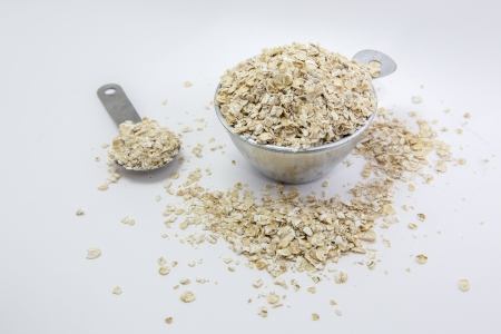 Oatmeal flakes in Stainless cup and spoon in white background