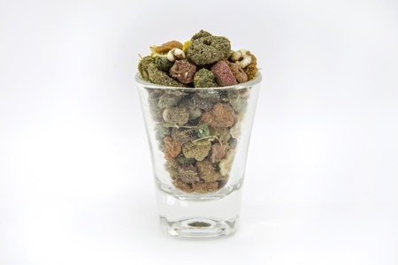 Pet food for guinea pigs or cavy in the glass on white background