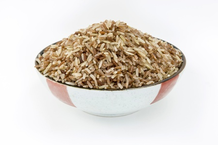 Uncooked Thai brown rice in bowl on white background Stock Photo
