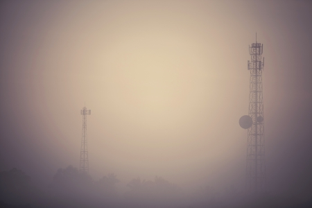 Vintage style telecom tower in the morning mist Stock Photo