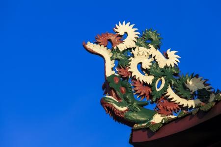dragon on roof of shrine in blue sky photo