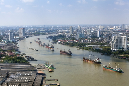 top view cargo ship on Chao Phraya river and city scape in Bangkok, Thailand photo