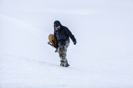 Snowboarder walking in the snow photo