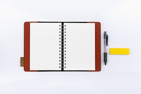 Open notebook with post it and pen on white background photo