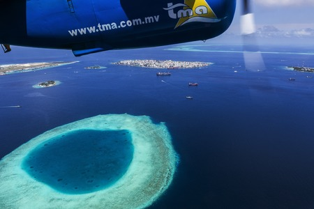 Indien Ocean Malddives - June 14, 2015 : Seaplane taxi fly over Atolls in Indian Ocean To transfer passengers to the hotel in the islands