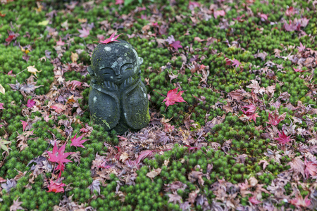 KYOTO, JAPAN - 19 NOVEMBER 2015: Stone statues in the moss garden at Zuiganzan Enkouji Temple in Kyoto, Japan. The temple has a beautiful garden with a pond and many maple trees.