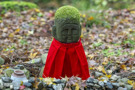 KYOTO, JAPAN - 19 NOVEMBER 2015: Stone statues and red hood in the garden at Sanzenin Temple in Kyoto, Japan