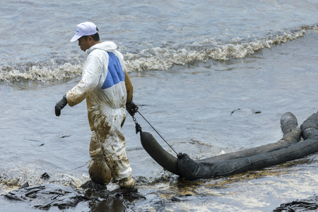RAYONG, THAILAND - JULY 31, 2013: A Worker in biohazard suits  used Oil Containment boom as cleaning crude oil spilled from the beach of Samet Island on July 31, 2013 in Rayong, Thailand.
