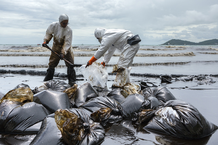 RAYONG, THAILAND - JULY 31, 2013: Workers remove and clean up crude oil spilled from Prao Bay on July 31, 2013 in Samet Island, Rayong, Thailand Editorial