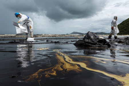 RAYONG, THAILAND - JULY 31, 2013: Workers remove and clean up crude oil spilled with absorbent paper from Prao Bay on July 31, 2013 in Samet Island, Rayong, Thailand
