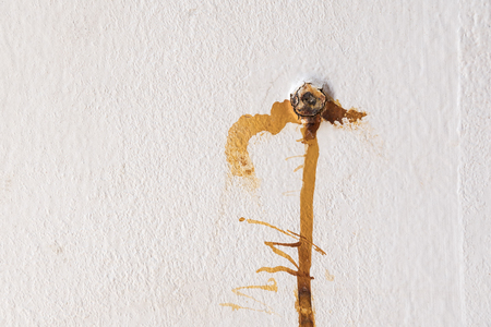 Rust stains from nail on the white cement wall