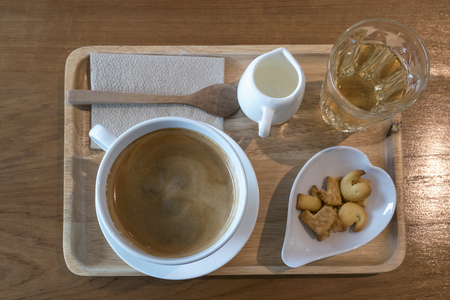 Coffee time in morning set hot americano with milk tea and cracker in wooden tray on wood table, top view Stock Photo