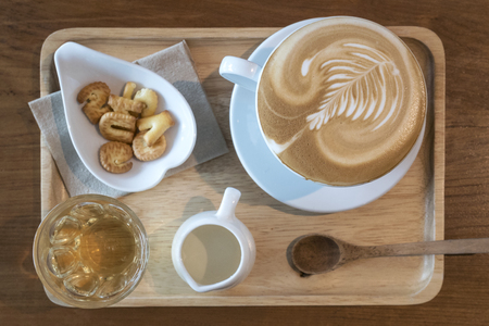 Coffee time in morning set hot latte art with milk tea and cracker in wooden tray on wood table, top view Stock Photo