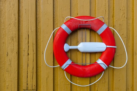 Orange lifebuoy with rope on a yellow wooden wall. Rescue equipment for emergency on water