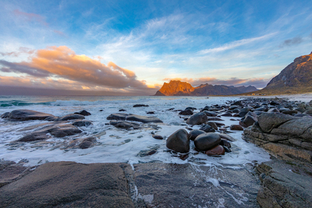 Rock beach and sea wave in evening sunlight at Uttakleiv Beach, This place is the most popular photographed in Leknes, Lofoten island, Norway Stock Photo