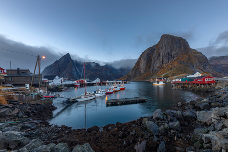 Fishing port and red rorbuer with Lilandstinden mountain at Hamnoy fishing village in the morning, Lofoten islands, Norway