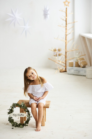 A beautiful little girl sitting on a wooden stool in a beautiful dress in the white room Banque d'images