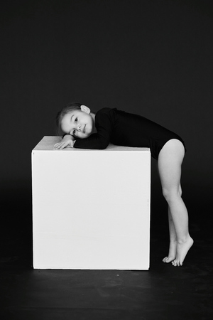 A portrait of beautiful little girl dressed in black tights on a white cube against dark background. Banco de Imagens