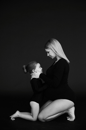 A portrait of beautiful pregnant mother with her little daughterirl dressed in black tights against dark background. Stockfoto
