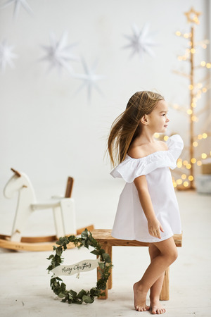 A beautiful little girl sitting on a wooden stool in a beautiful dress in the white room Banco de Imagens