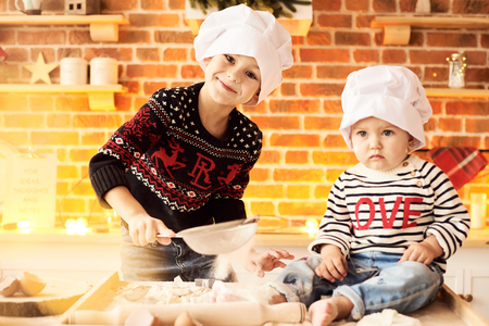 Children are cooked and played with flour and dough in the kitchen Фото со стока