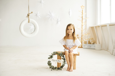 A beautiful little girl playing with a swing boat in the white room