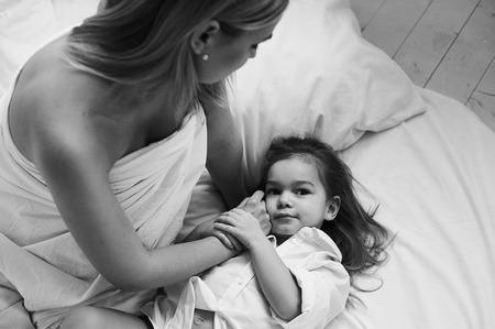 Een mooie zwangere moeder en dochter spelen 's ochtends op een wit bed. Stockfoto