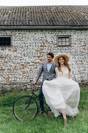 A beautiful young couple bride and groom with a bicycle near the old house