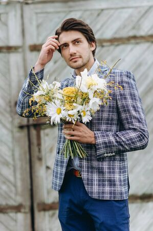 A young handsome groom holding a bouquet of daisies near old house outdoor
