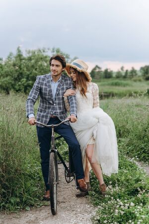 Beautiful young couple bride and groom walking in a field with a bicycle