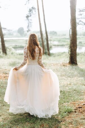 A beautiful young bride in white dress in a wood Stock Photo