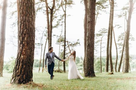 A young couple of brides walking in the pine forest Stock Photo
