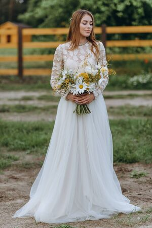 A beautiful young bride with a bouquet of daisies in a field