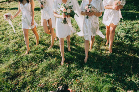 Faceless bridesmaids and bride in satin robes with bouquets in hands walk barefoot on the grass.