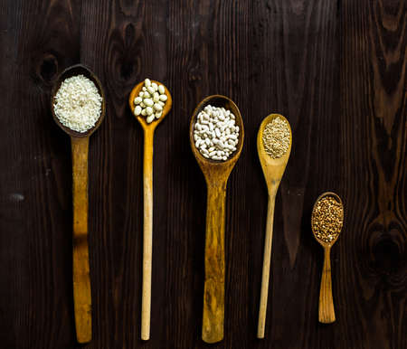 Top view of wooden spoons on which lie an assortment of different cereals on a wooden table.