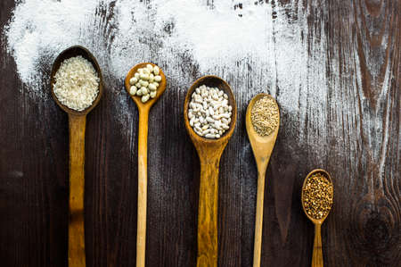 Top view of wooden spoons on which lie different cereals on a table sprinkled with flour. 免版税图像