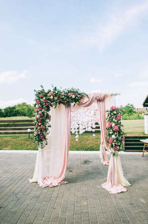 Elegant wedding arch made of pink flowers of hydrangea, roses and greenery on a spacious green lawn.