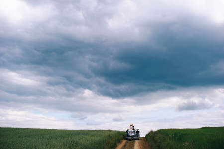 Newlyweds ride in a cabriolet in a field with poppies before a thunderstorm.