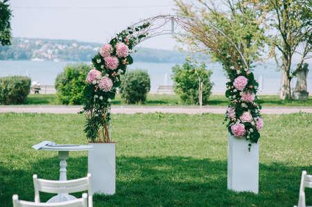 典雅的婚礼曲拱由绣球花,玫瑰和绿叶桃红色花制成在一个宽敞的绿色草坪。