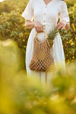 Girl holding a wicker bag with fruits.