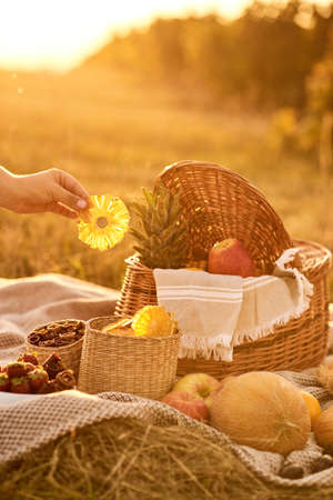 Female hand takes fruit chips from basket.