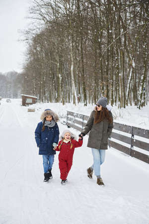 A portret of beautiful young caucasian mother with her children in winter near the house with a snow covered christmas trees in a background