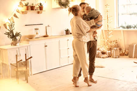 Young family dad, mom and their little son have a fun playing and cooking in the kitchen