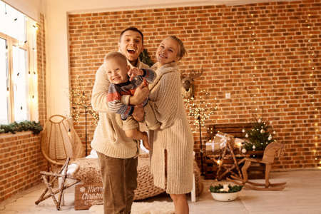 happy family mother father and child on Christmas morning in bedroom playing and have a fun Archivio Fotografico