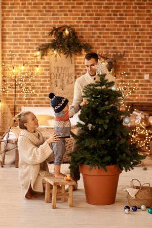 Happy young familyin bedroom decorates the Christmas tree Archivio Fotografico