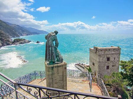 Statue of Saint Francis of Assisi petting a dog and looking out over Monterosso al Mar,  Italy