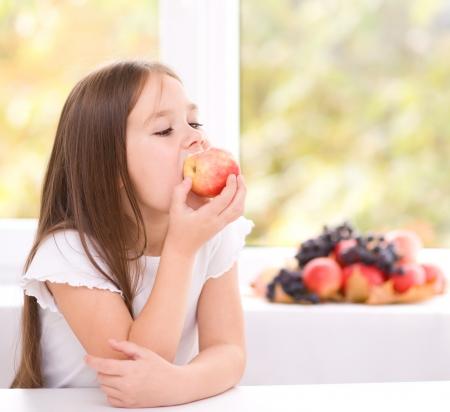 Cute little girl eating an apple Stock Photo