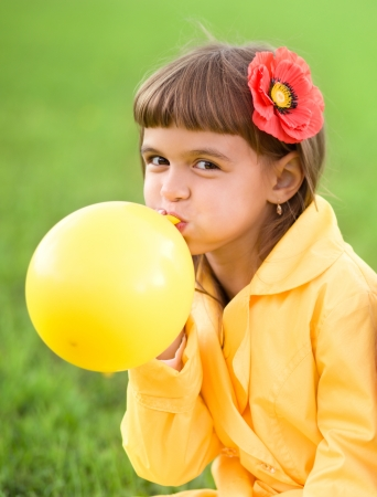 inflating: Little girl is inflating yellow balloon outdoors Stock Photo
