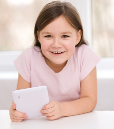 Happy little girl using tablet photo