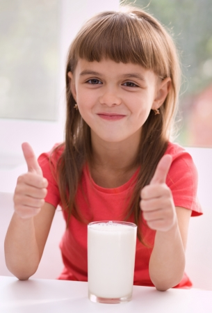Cute cheerful little girl with a glass of milk Stock Photo